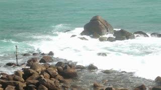 Waves covering rocks on beach in Sri Lanka