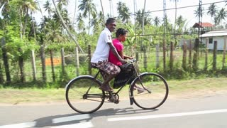 WELIGAMA, SRI LANKA - MARCH 2014: Local man and woman riding bicycle in Weligama. Cycling is the cheapest means of transport in the country.