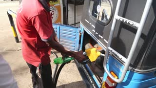 WELIGAMA, SRI LANKA - MARCH 2014: Local man putting petrol in tuktuk in Weligama. Tuktuks are an important means of transport in Sri Lanka.