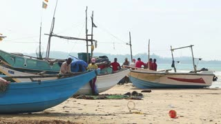 WELIGAMA, SRI LANKA - MARCH 2014: Timelapse of fishermen sorting nets on beach after long night working. They are finding it more difficult to make a living due to over-fishing.