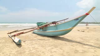 WELIGAMA, SRI LANKA - MARCH 2014: Traditional wooden fishing boat on beach in Weligama with people passing by.
