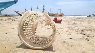 WELIGAMA, SRI LANKA - MARCH 2014: Trash washed up on shore in front of wooden fishing boast on beach.
