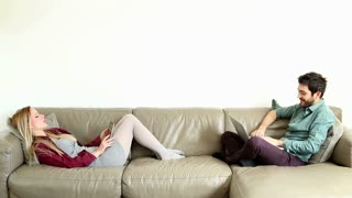 Woman and man sitting on couch and relaxing