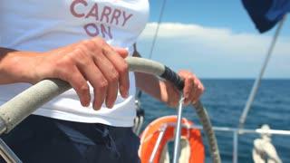 Woman at wheel steering sailboat on Adriatic sea in Croatia