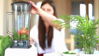 Woman blending vegetables in blender, in slow motion, graded