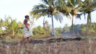 Woman burning dry grass on an open field.