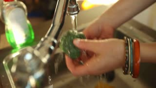 Woman cleaning broccoli in water under tap in sink