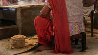 Woman collecting grilled Indian bread on pile at public kitchen in Amritsar.