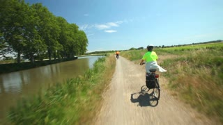 Woman cycling beside river on holidays