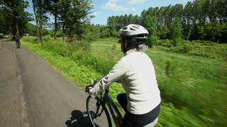 Woman cycling on road in countryside