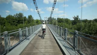 Woman cycling on road over suspension bridge