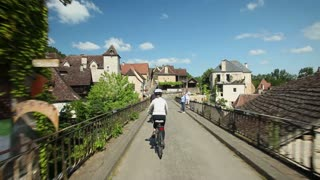 Woman cycling on road through village in France