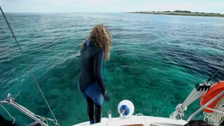 Woman diving and swimming in sea from boat