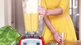 Woman in yellow dress pouring smoothie into glass at home