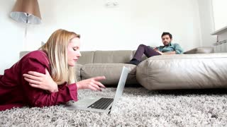 Woman laying on carpet looking at laptop with man sitting on couch in background