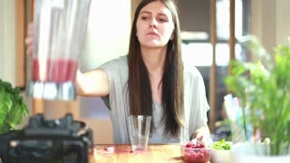 Woman pouring fruit smoothie into glass and drinking it, in slow motion, graded