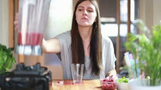 Woman pouring fruit smoothie into glass and drinking it, in slow motion