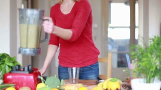Woman pouring smoothie into glass at home