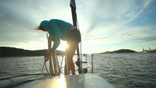 Woman preparing ropes on bow of sailboat on Adriatic sea in Croatia