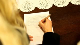 Woman signing wedding document
