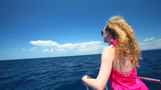 Woman sitting on bow of sailing boat enjoying view of sea