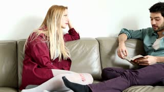 Woman sitting on comfortable couch speaking to handsome man