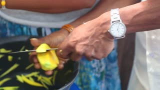 Woman vendor slicing mangos with knife for selling on her stand in Kandy, Sri Lanka