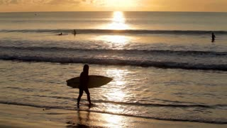 Woman walking at sunset with surfboard on beach in Bali