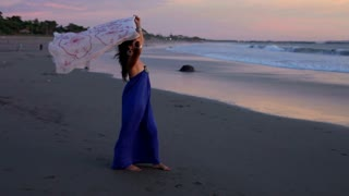 Woman walking on beach at sunset with fabric blowing in the wind