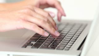 Woman's hands typing on laptop keyboard