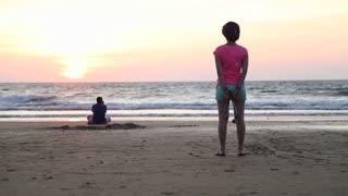 Women watching the ocean on sandy beach at sunset.