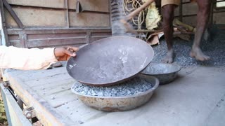 Workers filling bowls with pebbles and sand.