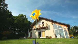 Yellow windmill spinning in wind in front of wooden house
