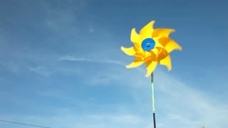 Yellow windmill spinning in wind on blue sky