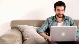 Young adult man sitting on couch in living room and having video chat