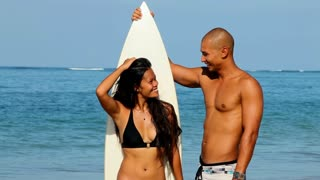 Young Asian couple with surfboard on beach