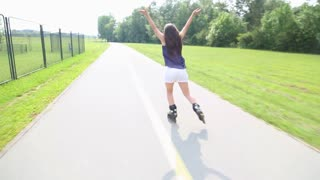 Young attractive woman rollerblading in park on a beautiful sunny day from back with hands in the air