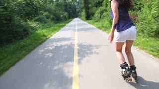 Young attractive woman rollerblading in park on a beautiful sunny day from back