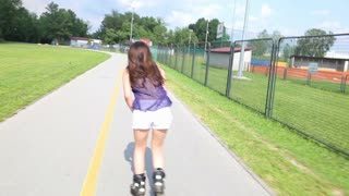 Young attractive woman rollerblading in park on a beautiful sunny day, lifting arms in the air.