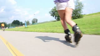 Young attractive woman rollerblading in park on a beautiful sunny day, view of legs