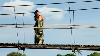 Young beautiful asian woman standing on suspension bridge with long colourful dress