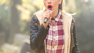 Young beautiful woman singing with a microphone in hands, graded