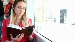 Young beautiful woman sitting in tram, listening to music and reading the book