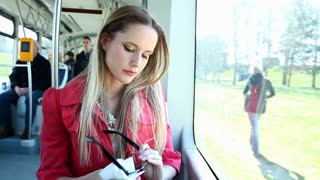 Young blond woman riding tram, cleaning her glasses