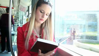 Young blond woman riding tram, reading book on sunny day
