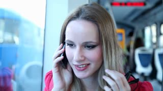 Young blond woman riding tram, talking on mobile, phone, cell, holding glasses