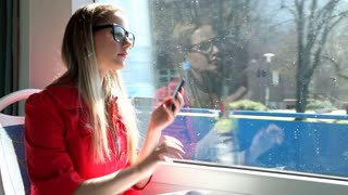 Young blond woman riding tram, talking on mobile, phone, cell