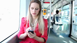 Young blond woman riding tram, typing on mobile, phone, cell and talking