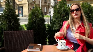 Young blond woman sitting in coffee shop, drinking beverage