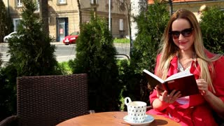 Young blond woman sitting in coffee shop, reading book